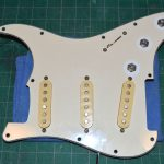 The '77 pickguard showing its age before reinstalling the knobs